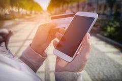 Pagar com o smartphone e o cartão de crédito exteriores Foto de Stock Royalty Free