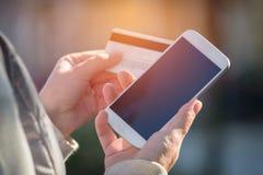 Pagar com o smartphone e o cartão de crédito exteriores Imagem de Stock Royalty Free