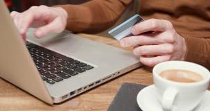 Pagar com um cartão em linha em uma loja do coffe video estoque