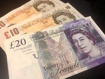 Pagar em notas da moeda de libra esterlina de Reino Unido imagens de stock royalty free