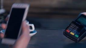 Pagar fêmea através do telefone esperto usando a tecnologia de NFC Close-up 4K vídeos de arquivo