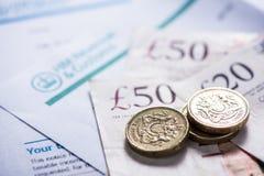 Pagar impuestos en Reino Unido, billetes y monedas esterlinas Fotos de archivo libres de regalías