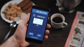 Pagar un receipe de la tienda con un smartphone app En el marco de las manos del ` s del hombre, una persona paga compras en un e metrajes