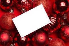 Page blanc sur les babioles rouges de Noël Photographie stock libre de droits