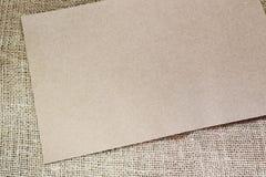 Page blanche d'un carton sur la toile de jute Image stock