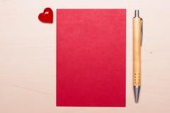 Page blanche de coeur et de stylo de papier sur la table Images stock