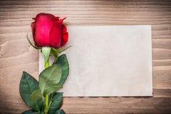 Page blanche de papier et de bouton de rose rouge sur le conseil en bois Photos libres de droits