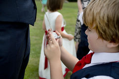Page boy looking at the grooms pocket watch at a wedding Royalty Free Stock Photo