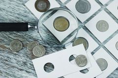 Page with collector`s coins in the pockets, and a magnifying glass Stock Photo