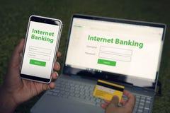 Page d'accueil passée en revue par homme de service bancaire d'Internet sur son smartphone et ordinateur portable tenant la carte image stock