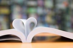page de nouveau livre dans la forme de coeur avec le fond de bibliothèque, amour dans le va Image stock