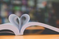 page de nouveau livre dans la forme de coeur avec le fond de bibliothèque, amour dans le va Image libre de droits