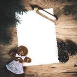 Page de papier blanche sur un plancher en bois avec un crayon et des décorations de Noël avec un bonhomme en pain d'épice image libre de droits