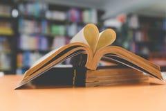 page de vieux livre dans la forme de coeur avec le fond de bibliothèque, amour Photographie stock