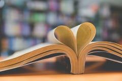 page de vieux livre dans la forme de coeur avec le fond de bibliothèque, amour dans le va Images stock