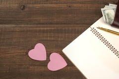 Page en spirale vide de bloc-notes, coeurs, portefeuille sur le Tableau en bois Backgro Photo libre de droits