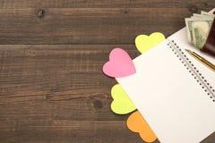 Page en spirale vide de bloc-notes, coeurs, portefeuille sur le Tableau en bois Backgro Photographie stock