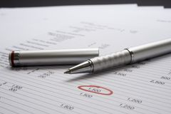 Page of figures with pen. Page of figures with single figure highlighted in red with a pen and pen lid on the paper royalty free stock image