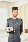 Page in hotel with food cloche. Page in hotel serving food with cloche in hotel room Stock Photography