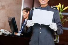 Page in hotel holding blank sign. Page in hotel holding empty white blank sign in his hands Royalty Free Stock Photo