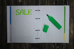 Page of Notepad with inscription Sale on wooden background and a marker. Stock Photography