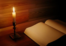 Page of old book illuminated with candle Royalty Free Stock Image