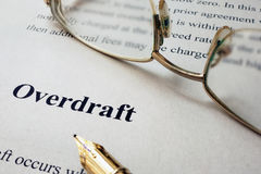 Page of paper with words Overdraft. Page of paper with words Overdraft and glasses Royalty Free Stock Photos