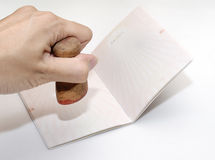 Page of passport. It is a empty chinese passport. A hand is taking a stamp. Isolated Royalty Free Stock Image