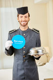 Page with service guarantee in hotel room. Page with service guarantee badge and food cloche in a hotel room Stock Image