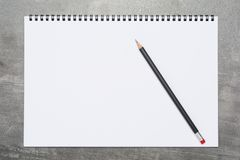 Page vide d'un carnet à dessins avec un crayon noir sur une surface grise photographie stock libre de droits