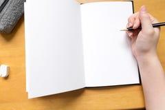 Page vide dans le carnet à dessins avec la main Image stock