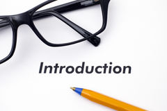 Page with word Introduction with glasses and pen. Page with word Introduction and glasses and ballpoint pen Stock Photo