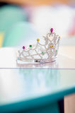 Pageant crown with gems. Sparkly crown on blue coloured table Stock Photos