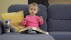 Pages émotives de tour de bébé de livre se reposant sur le sofa avec l'ami d'ours de nounours banque de vidéos