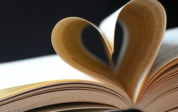 Pages of a book curved into a heart Stock Photos