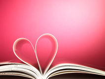 Pages of a book curved into a heart shape. On pink Stock Image
