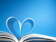 Pages of a book curved into a heart shape. On blue background royalty free stock image