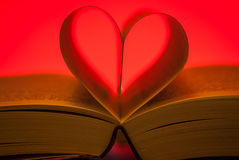 Pages of a book forming a heart on red background Royalty Free Stock Photography