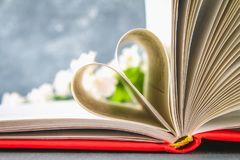 The pages of the book in the red cover are made in the form of a heart. The concept of Valentine's Day. The pages of the book in the red cover are made in the Royalty Free Stock Photo