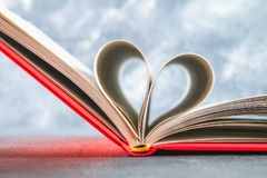 The pages of the book in the red cover are made in the form of a heart. The concept of Valentine's Day. The pages of the book in the red cover are made in the Stock Images