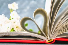 The pages of the book in the red cover are made in the form of a heart. The concept of Valentine's Day. The pages of the book in the red cover are made in the Royalty Free Stock Images