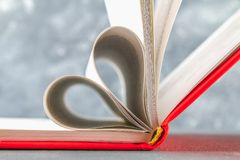 The pages of the book in the red cover are made in the form of a heart. The concept of Valentine's Day. The pages of the book in the red cover are made in the Stock Image