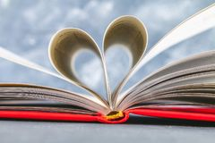 The pages of the book in the red cover are made in the form of a heart. The concept of Valentine's Day. The pages of the book in the red cover are made in the Royalty Free Stock Photography