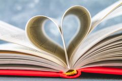 The pages of the book in the red cover are made in the form of a heart. The concept of Valentine's Day. The pages of the book in the red cover are made in the Royalty Free Stock Photos
