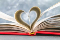 The pages of the book in the red cover are made in the form of a heart. The concept of Valentine's Day. The pages of the book in the red cover are made in the Stock Photography