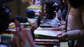 Pages de rotation de livre de femme au magasin de détail, choix actuel pour l'ami, passe-temps banque de vidéos