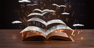 Pages and glowing letters flying out of a book Royalty Free Stock Image
