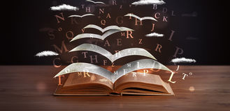 Pages and glowing letters flying out of a book Royalty Free Stock Photography