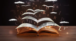 Pages and glowing letters flying out of a book Royalty Free Stock Photo