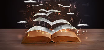Pages and glowing letters flying out of a book Royalty Free Stock Photos